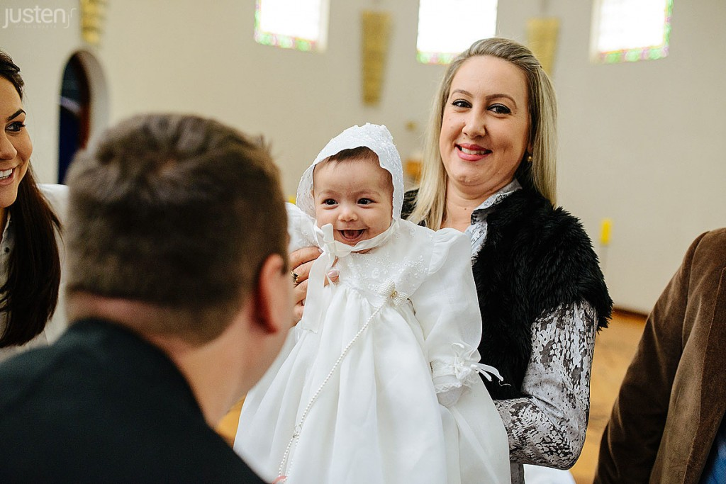 madrinha segurando afilhada no colo com roupa de batismo