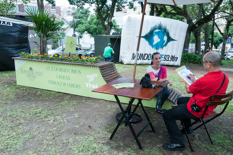 Caricaturista desenhando uma convidada em um espaço de lazer promovido pela THÁ.