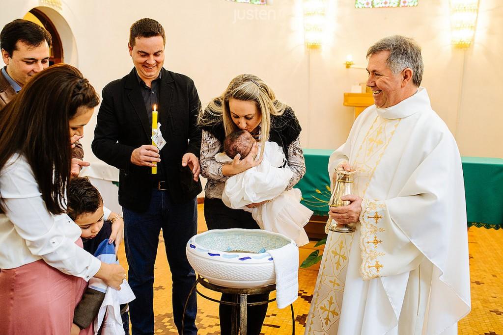 Madrinha beijando a afilhada em batismo no Asilo São Vicente de Paulo